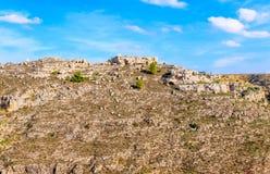 由石头构成的教会,历史建筑 马泰拉Sassi 巴斯利卡塔在蓝天下 图库摄影