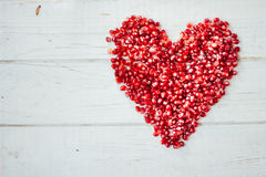 由石榴种子做的红色心脏-情人节标志 免版税库存图片