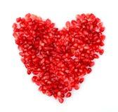 由石榴,在白色的石榴汁糖浆种子做的红色心脏  免版税库存图片