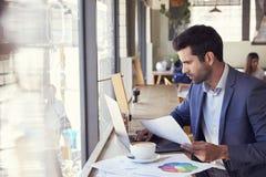 由研究在咖啡店的膝上型计算机的窗口的商人 免版税库存照片