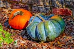由砖墙的两个装饰南瓜在秋叶 免版税图库摄影