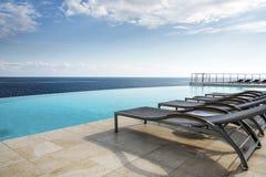 由空的无限水池的Sunbeds 免版税图库摄影