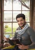 由窗口供以人员有片剂和杯子的佩带的围巾在乡下 库存图片