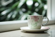 由窗口的一个咖啡茶杯有室外看法 免版税库存图片