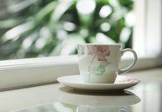 由窗口的一个咖啡茶杯有室外看法 库存图片