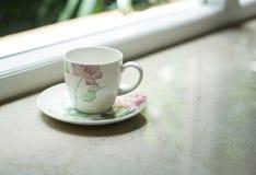 由窗口的一个咖啡茶杯有室外看法 免版税库存照片