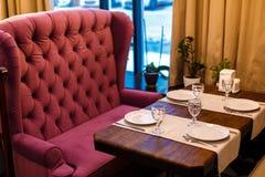由窗口的一张桌在咖啡馆,桌设置-葡萄酒伯根地沙发,棕色颜色一张木桌  库存照片