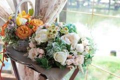 由窗口的两美丽的婚礼花束 免版税库存照片