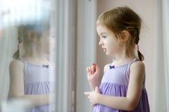 由窗口的可爱的小女孩 免版税图库摄影