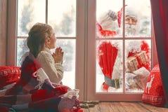 由窗口的女孩在圣诞节 免版税库存照片
