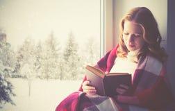 由窗口的愉快的女孩阅读书在冬天 免版税库存图片