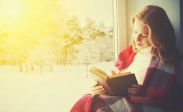 由窗口的愉快的女孩阅读书在冬天 免版税库存照片