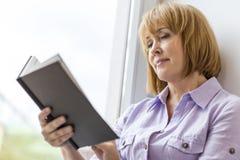 由窗口的成熟妇女阅读书在家 免版税库存图片