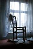 由窗口的椅子 免版税库存图片