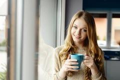由窗口的美丽的微笑的白肤金发的妇女饮用的咖啡 免版税库存图片