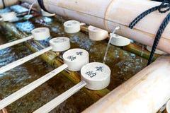 由竹瓢的神道的信徒的Omairi洗涤的仪式在Fushimi Inari,京都,日本 免版税库存图片