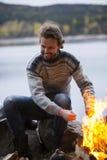 由篝火的人温暖的手在湖边野营 库存照片