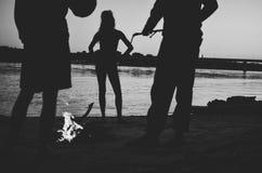 由篝火的黑白现出轮廓的人在夜野营的海滩 免版税库存照片