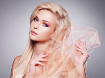 由米黄织品的肉欲的白肤金发的妇女覆盖物 免版税库存图片