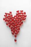 由红色软的药片做的心脏 库存照片