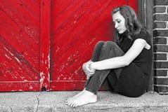 由红色门的哀伤的十几岁的女孩 免版税库存图片