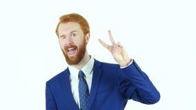 由红色头发胡子商人,白色背景的胜利标志 股票录像