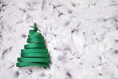 由绿色丝带做的圣诞树在五颜六色的背景 免版税库存照片