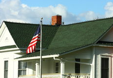 由绿色木瓦之家的美国国旗 免版税库存照片