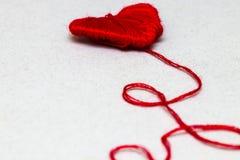 由羊毛做的红色心脏形状标志在白色 库存照片