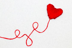由羊毛做的红色心脏形状标志被隔绝在白色 免版税库存图片