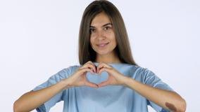 由美丽的女孩,白色背景的手工制造心脏标志在演播室 库存图片