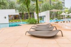 由美丽的水池的四把好的象叶子的休息的椅子 免版税库存照片