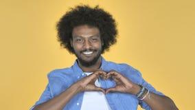 由美国黑人的人的手工制造心脏黄色背景的 股票录像