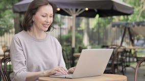 由老妇人的视频聊天通过膝上型计算机,坐在室外咖啡馆 影视素材