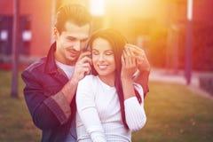 年轻由耳机的夫妇听的音乐在约会期间 免版税图库摄影
