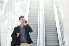由自动扶梯的英俊的商人在电话 免版税库存照片