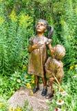 由艺术家詹姆斯海尔的一个儿童大小雕塑给权了:对于哪些站立,位于对村庄绿园的入口没有 免版税图库摄影