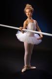 由芭蕾酒吧的微笑的芭蕾学生 库存照片