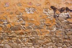 由花岗岩岩石和被剥去的膏药做的老石墙 库存图片