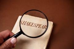 由莎士比亚所著的书通过放大镜 库存照片