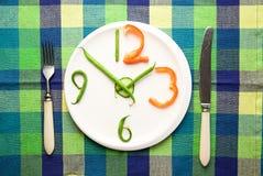 由菜做的手表在板材 免版税图库摄影