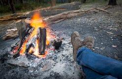 由营火的温暖的脚 免版税库存图片