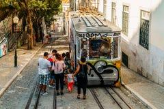 由葡萄酒的游客旅行缆索铁路在里斯本市狭窄的老街道上  图库摄影