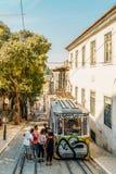 由葡萄酒的游客旅行缆索铁路在里斯本市狭窄的老街道上  库存图片