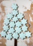 由蓝色姜饼曲奇饼和肉桂条做的圣诞树在轻的木背景 土气样式 免版税库存图片