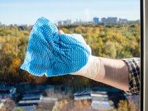 由蓝色旧布的季节性清洁家玻璃窗 免版税库存照片
