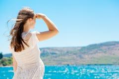 由蓝色海运的年轻人孕妇 免版税库存图片