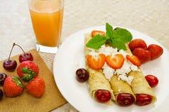 由薄煎饼做的点心充塞用凝乳酪用草莓和樱桃在一块白色板材的一张桌上 免版税库存图片