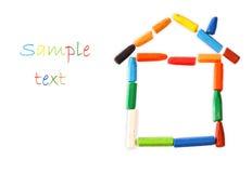 由蜡笔做的议院形状。家庭concept.family概念。 图库摄影