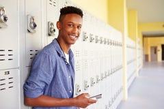 由衣物柜的男性高中学生使用手机 库存照片